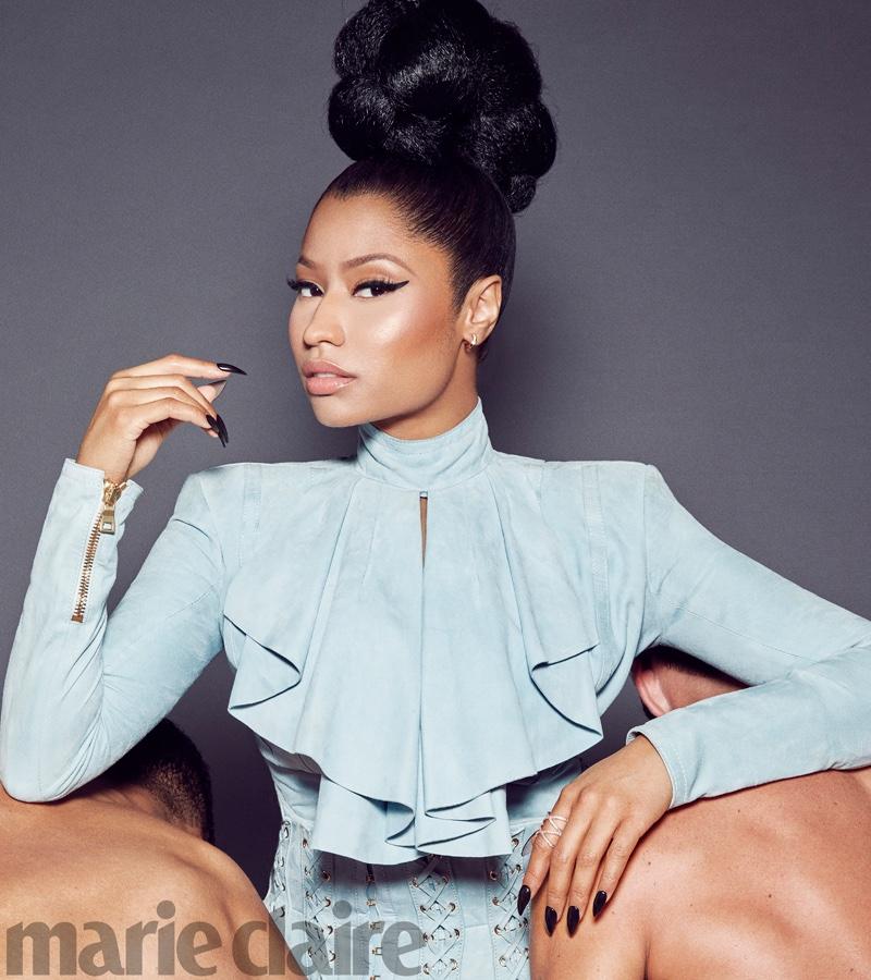 Posing with a high top knot hairstyle, Nicki Minaj wears Balmain ruffled top