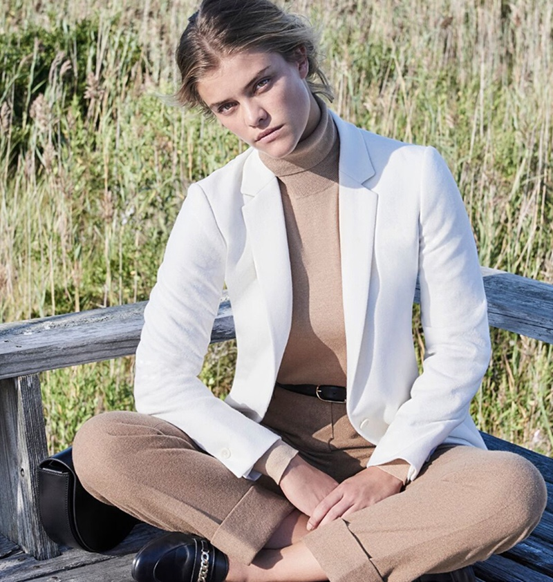 The model looks sharp in a white blazer with a camel turtleneck and pants