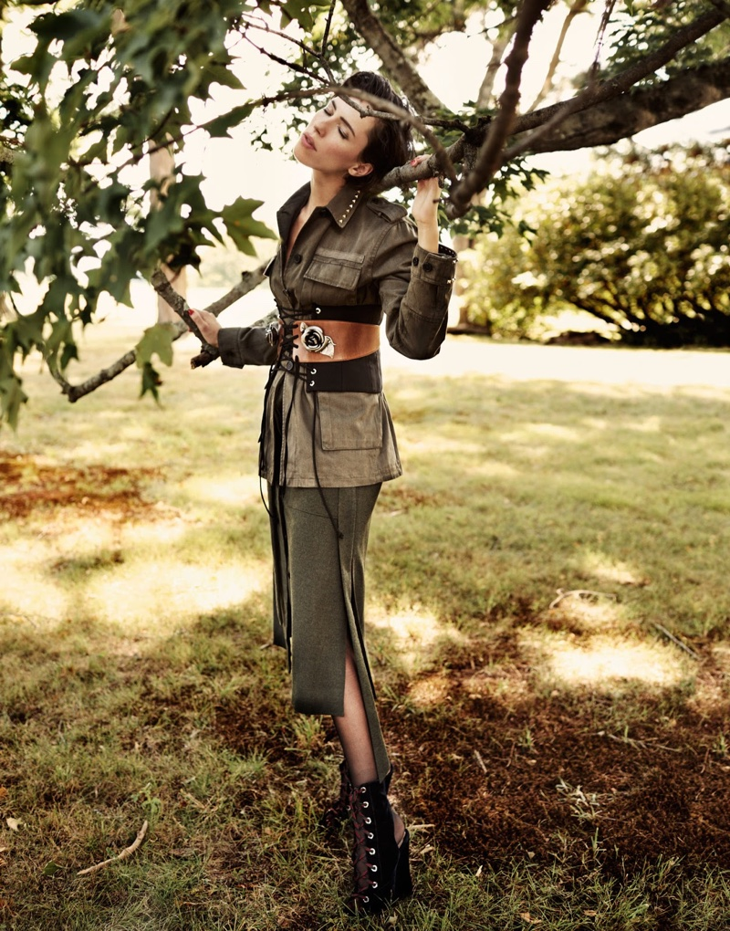 Posing next to a tree, Rebecca Hall wears Valentino Jacket, Ellery corset, Tibi skirt with boots and belt by Prada