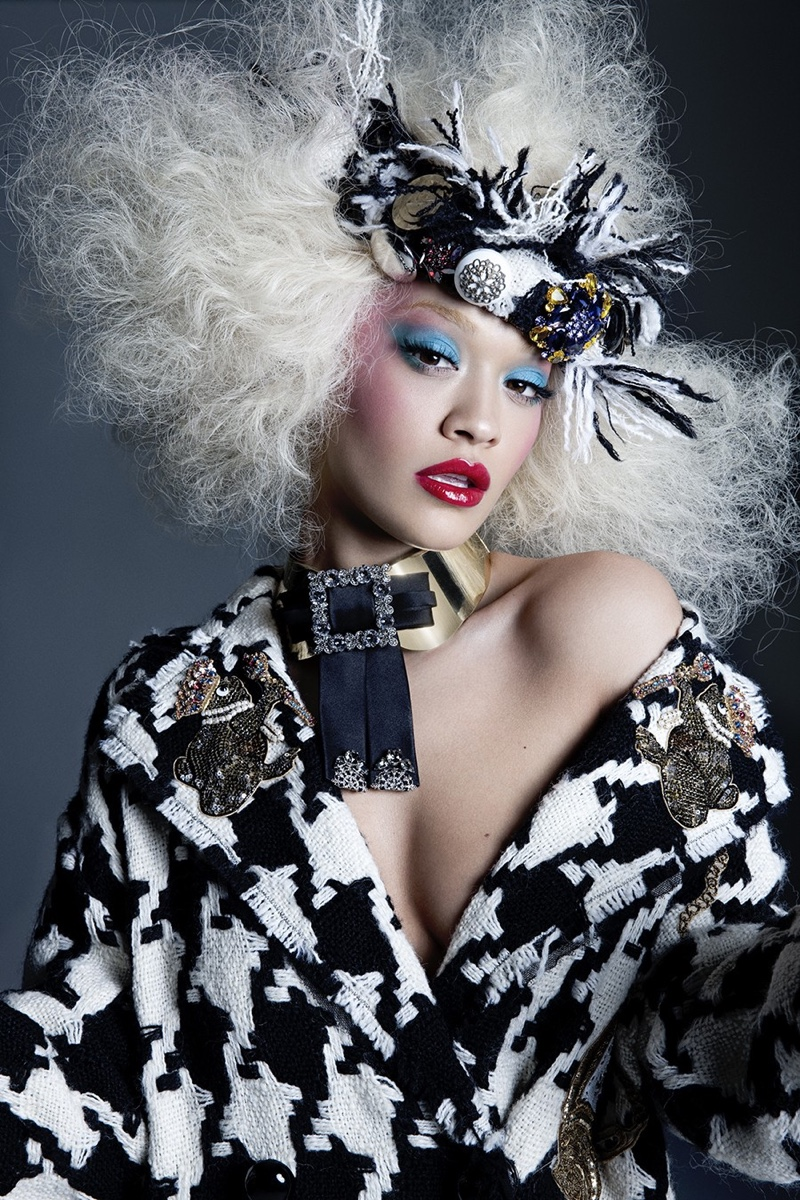 Wearing a white wig, Rita Ora poses in Dolce & Gabbana coat, necklace and headpiece