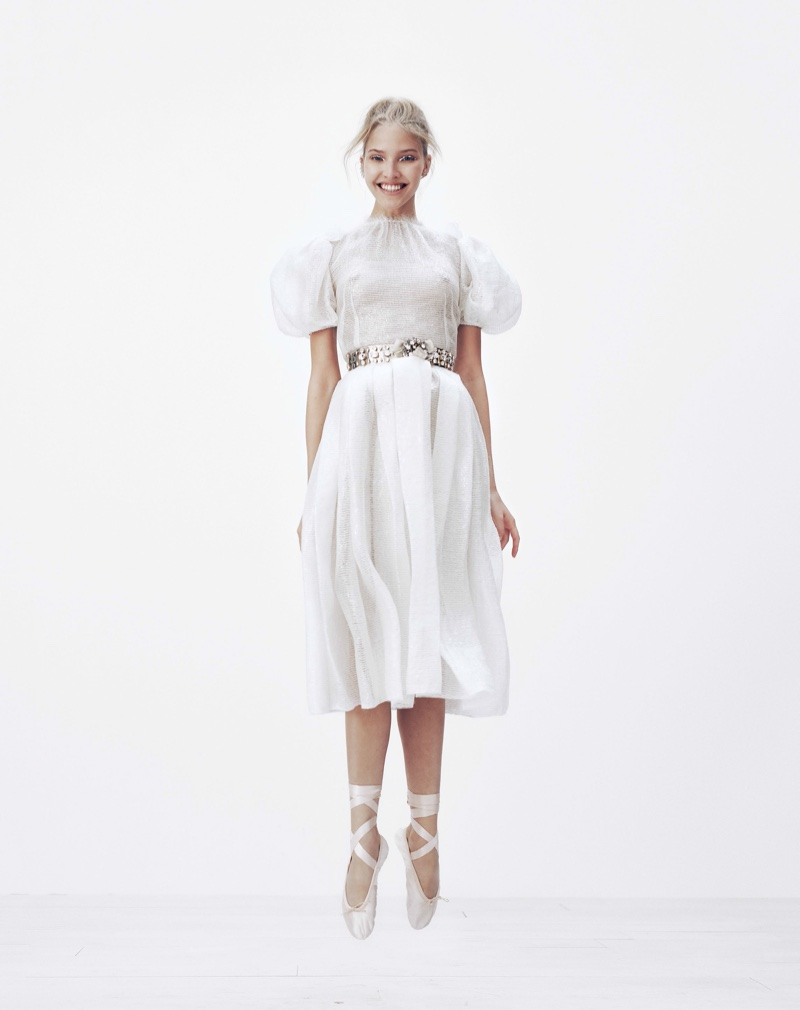Model Sasha Luss poses in white Dolce & Gabbana dress with puffed sleeves