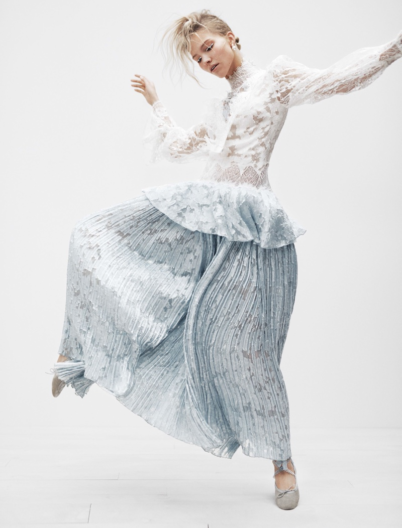 The model poses in a lace top and micropleated skirt