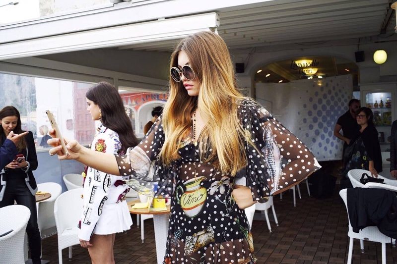 Thylane Blondeau checks her phone behind-the-scenes at Dolce & Gabbana's spring 2017 campaign