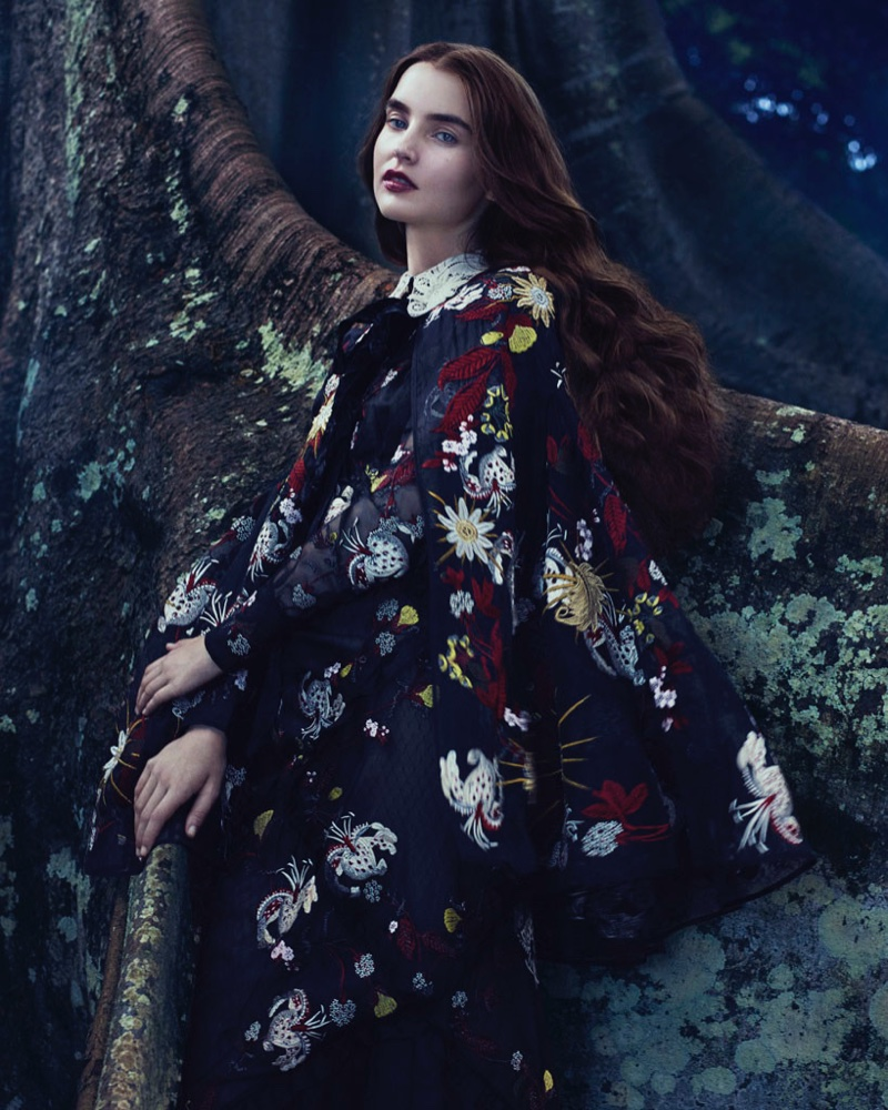 Covering up, the model poses in an Erdem cape and dress with floral print