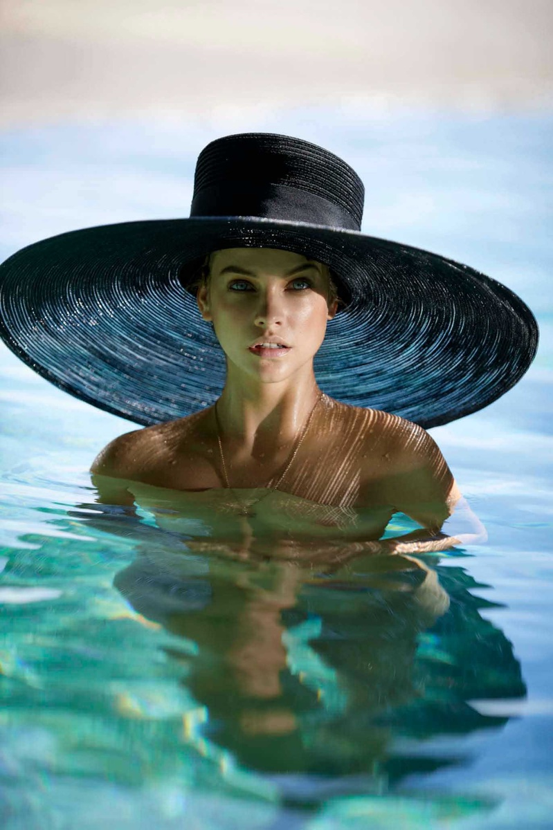 Posing in a pool, Barbara Palvin wears a wide-brimmed sun hat