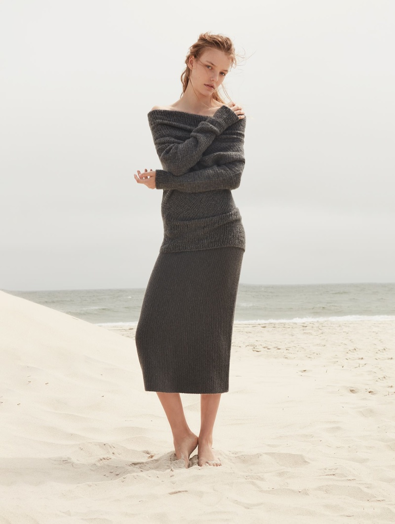 Posing on the beach, Roos Abels wears Calvin Klein Collection off-the-shoulder cashmere sweater and skirt