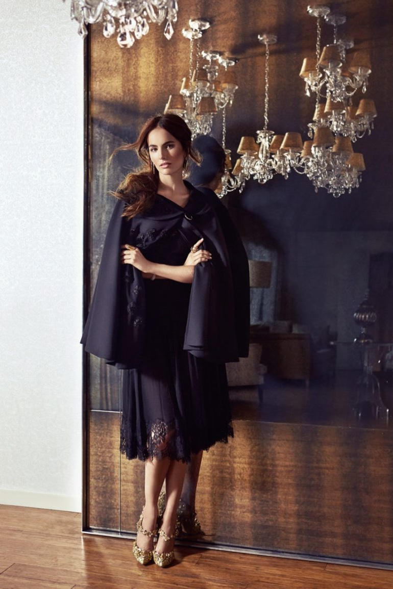 Wearing a cape and black lace dress, Camilla Belle poses in a chic look