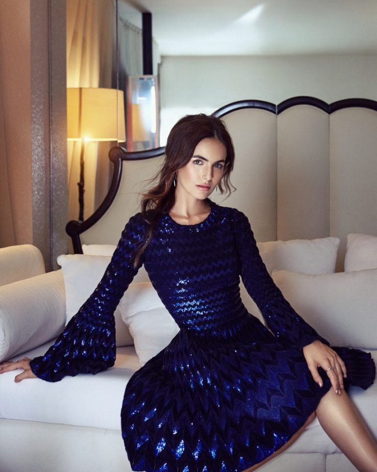 Posing on a bed, Camilla Belle wears a sequined dress
