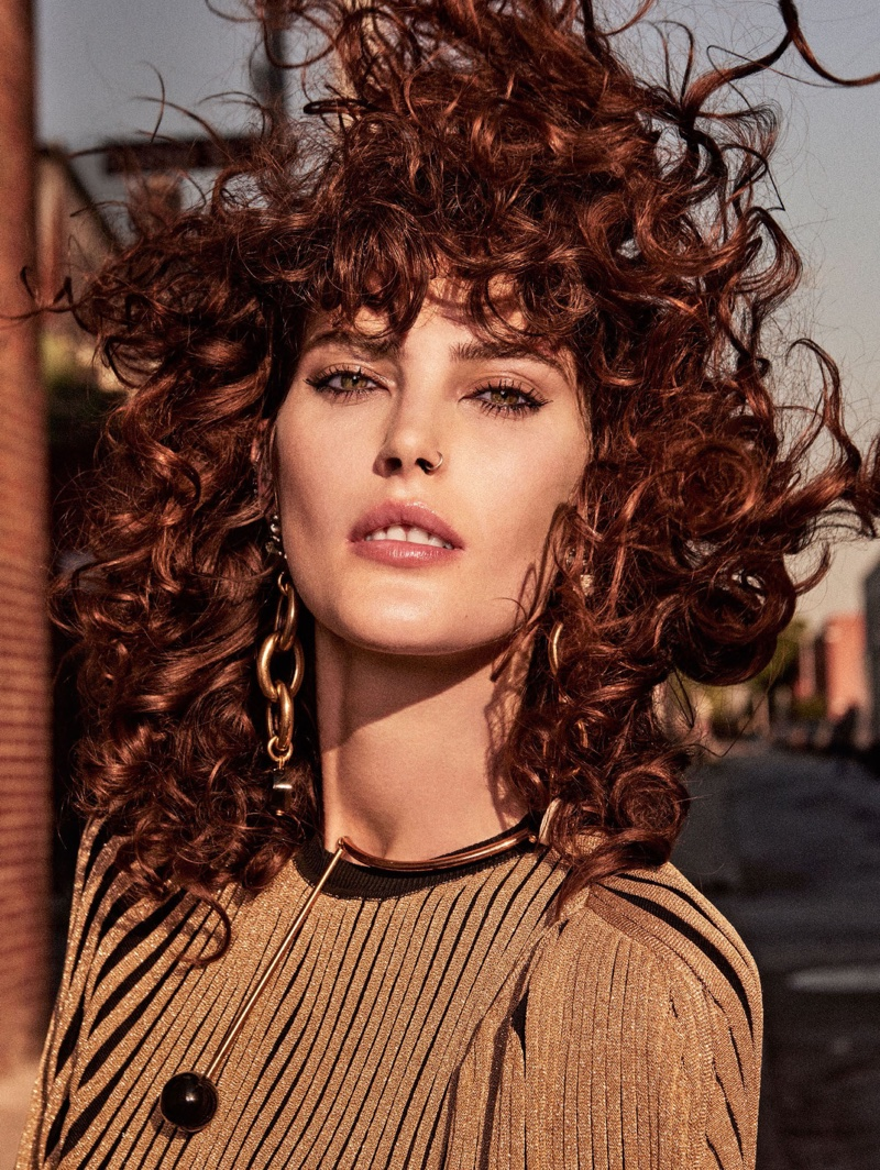 Wearing a curly hairstyle, Catherine McNeil poses in Sonia Rykiel dress with Marni earrings