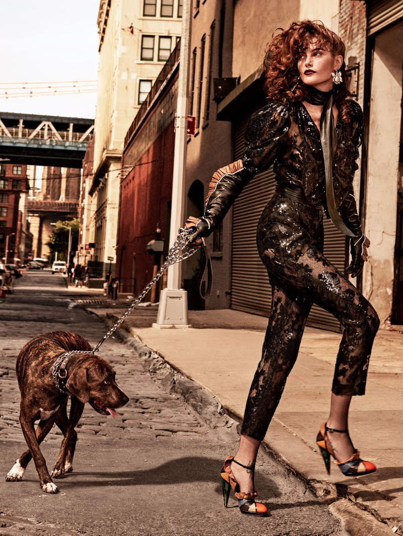Posing with a dog, Catherine McNeil wears Rodarte sequined top and pants with leather shoes, earrings and glove