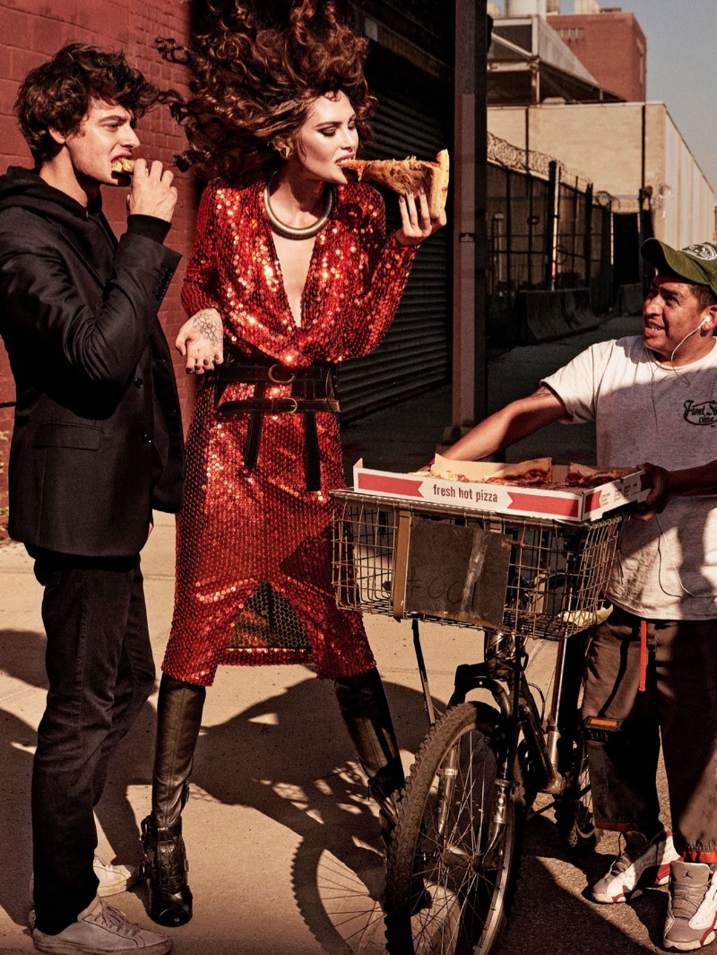 Taking a bite of pizza, the model wears sequined dress, leather boots and belt by Tom Ford