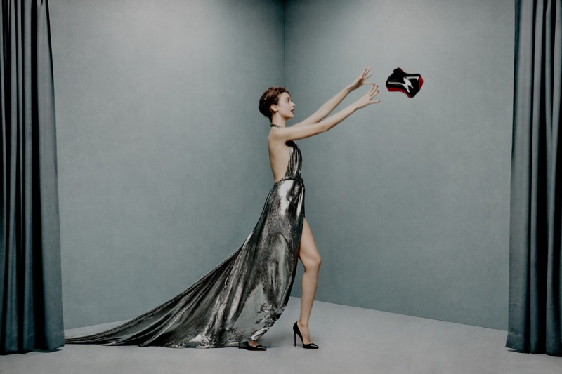 Model poses with Christian Louboutin Shoepeaks clutch bag and So Kate pumps