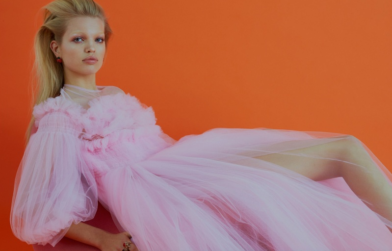 Lounging on a couch, Daphne Groeneveld wears fluffy pink gown