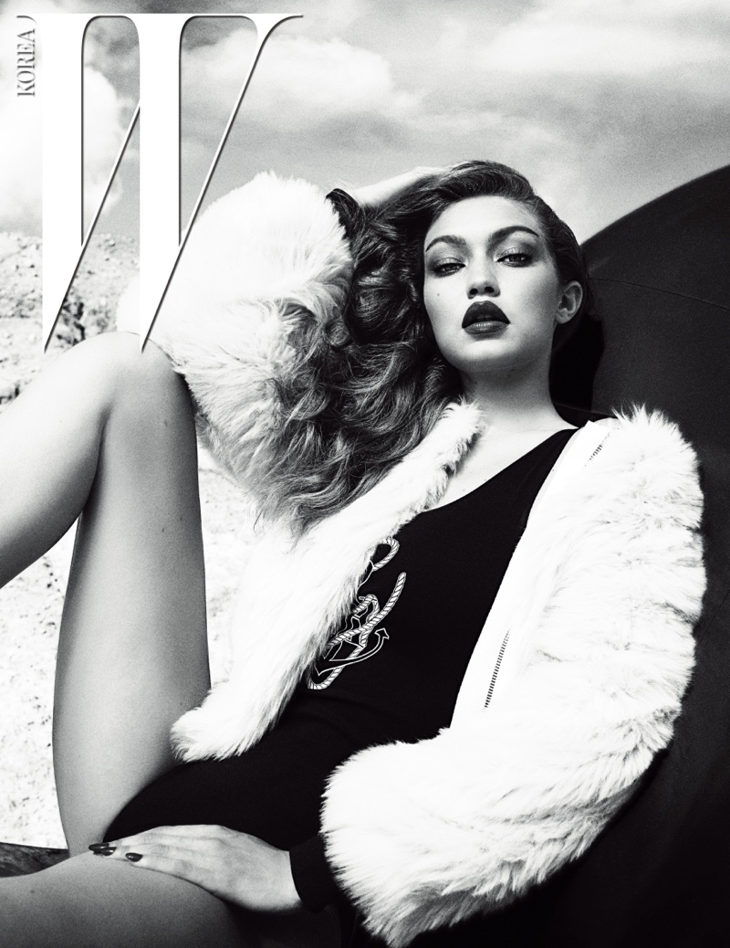 Photographed in black and white, Gigi Hadid poses in Miu Miu jacket with Tommy Hilfiger bodysuit