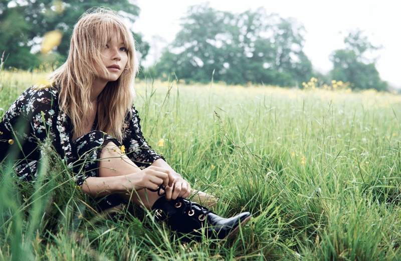 In a field of grass, Haley Bennett wears Dior dress with lace-up boots
