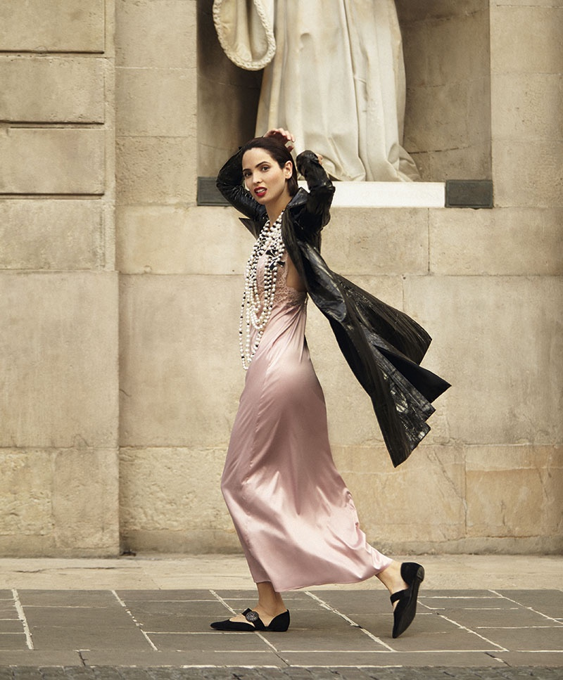 Walking down the street, the model wears a black jacket with a pink slip dress