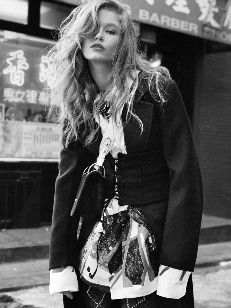 Model Hollie-May Saker wears Prada jacket over printed shirt and leggings