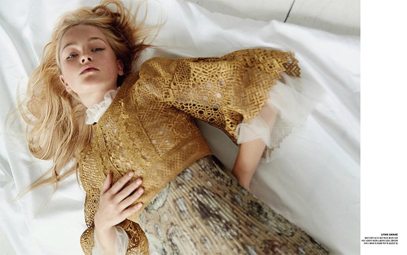 Laying in bed, Jean Campbell wears lace top with pleated skirt
