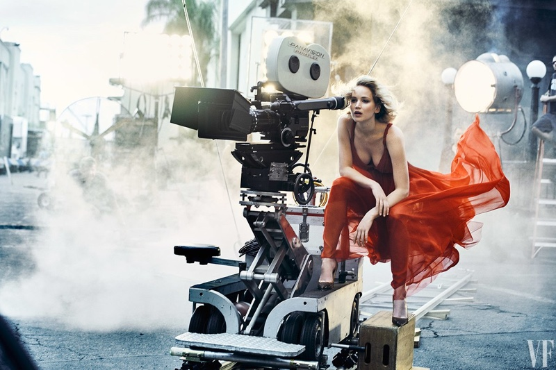 Posing behind a camera, Jennifer Lawrence wears a Dior dress and heels