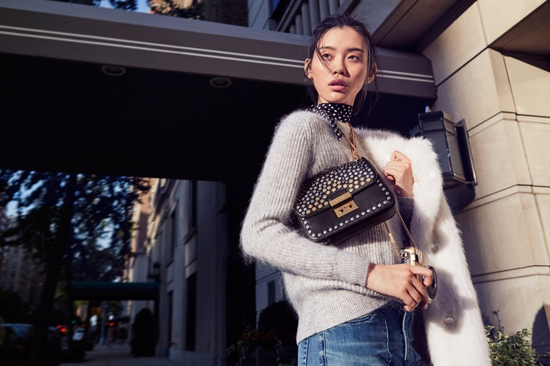 Model Ming Xi poses with Michael Kors' Sloan Editor bag