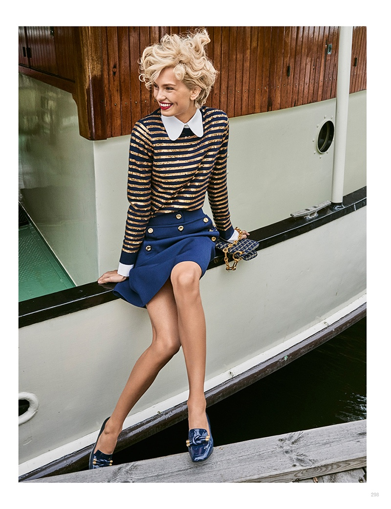Sitting on a dock, Romee Strijd models Michael Kors Collection striped top, embellished skirt and loafers