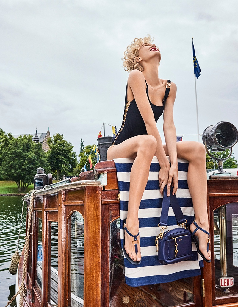 Model Romee Strijd wears Michael Kors Collection swimsuit, sandals and bag