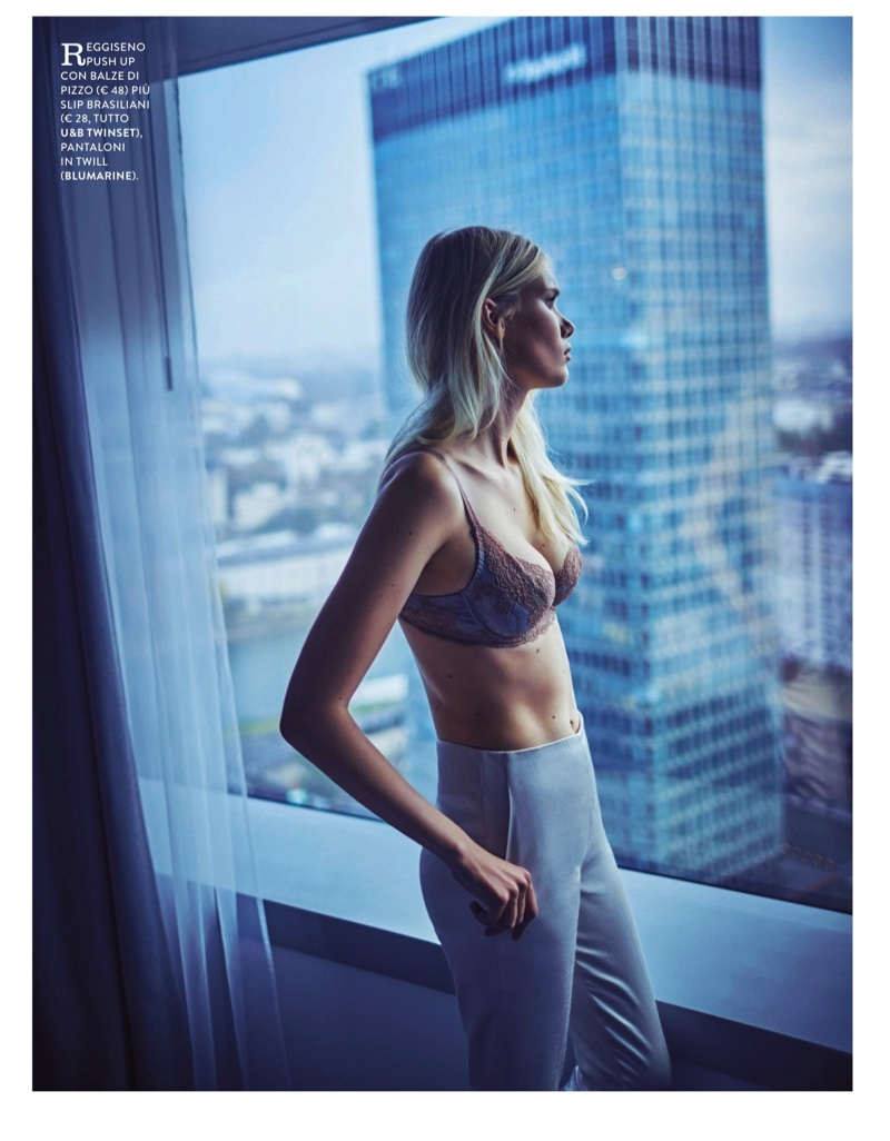Looking out a window, the blonde wears Twinset pushup bra with Blumarine twill pants
