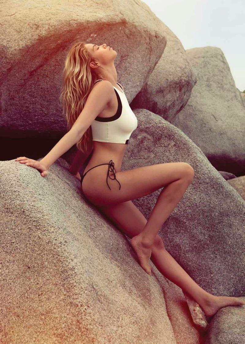 Posing on rocks, Hailey Clauson wears white tank top and black bikini bottoms