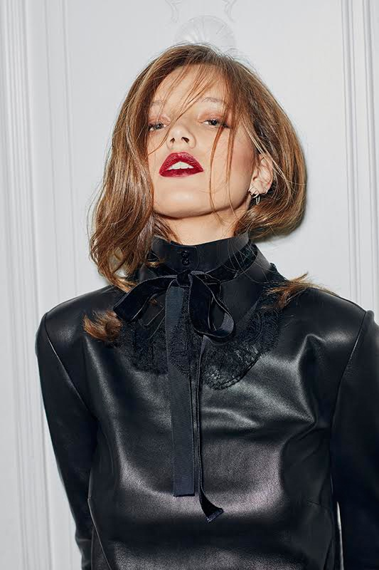 Wearing red lipstick, Heloise Giraud models a black leather dress