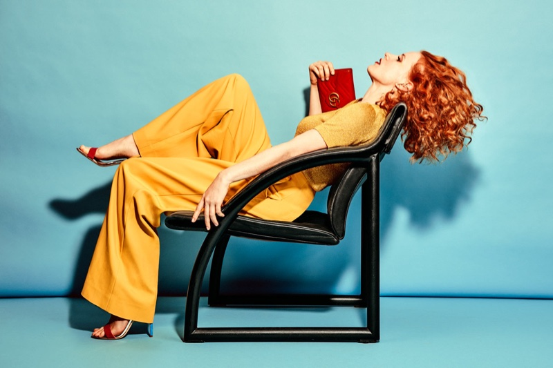 Lounging in a chair, Jessica Chastain wears Missoni t-shirt, Tibi pants, Giuseppe Zanotti sandals and Gucci shoulder bag