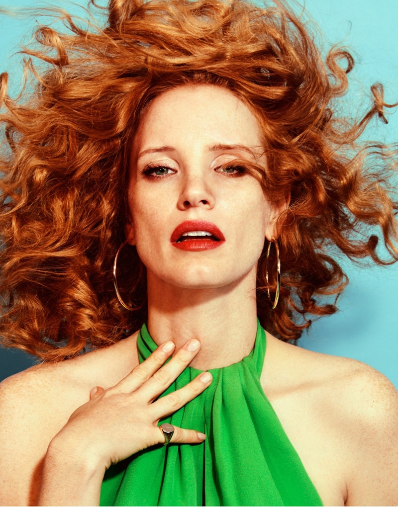 Wearing her hair in bold curls, Jessica Chastain poses in Emilio Pucci dress and Jennifer Fisher earrings
