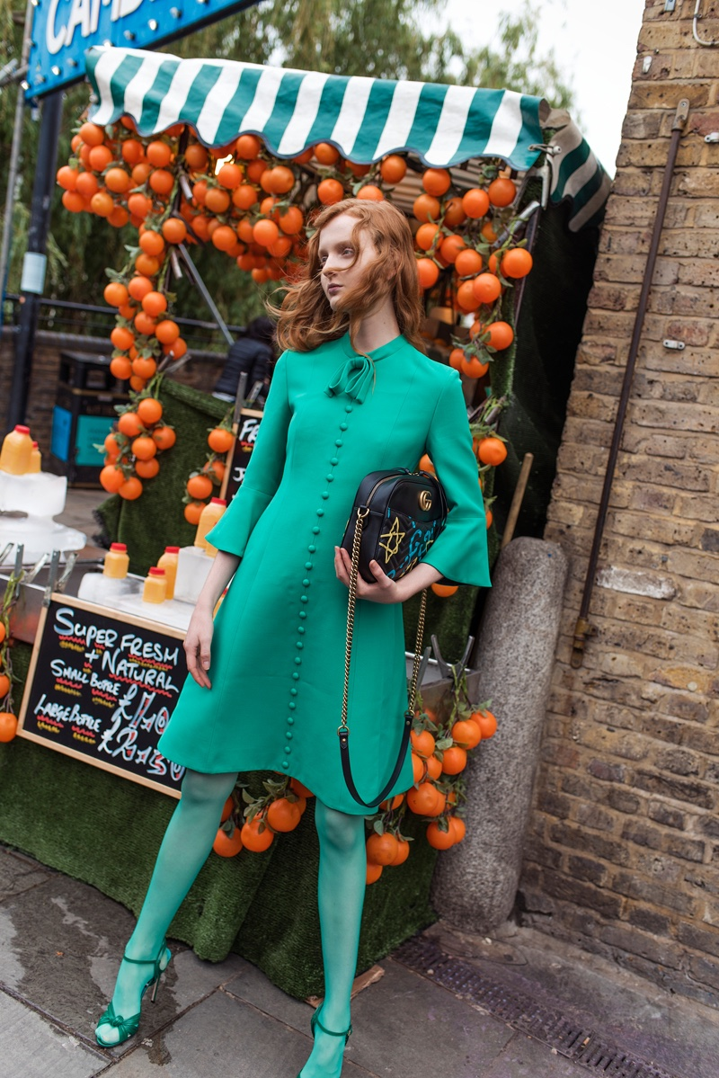 Wearing a teal ensemble from Gucci, Madison Stubbington poses in front of an orange display