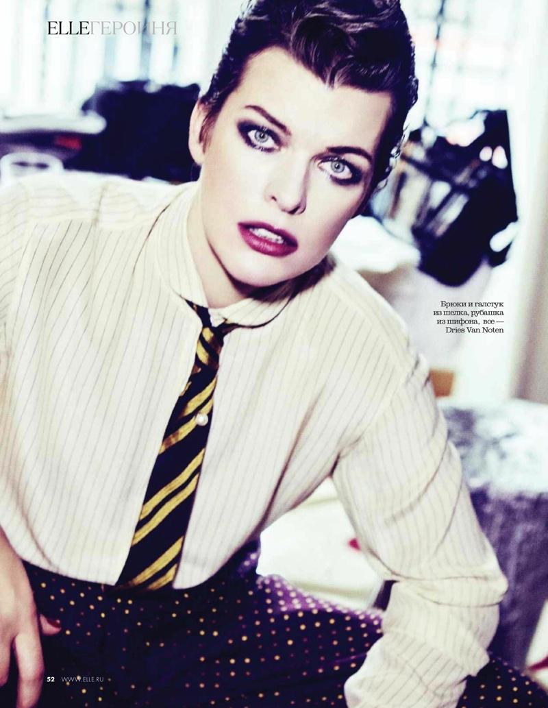 Posing in a menswear inspired look, Milla Jovovich wears Dries Van Noten shirt, tie and pants