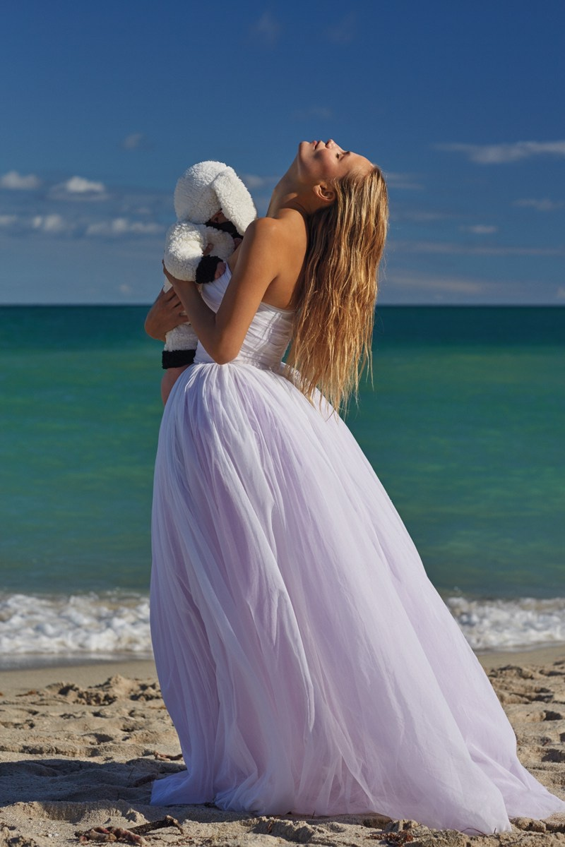 Posing on the sand, Natasha Poly models Juan Gatti dress