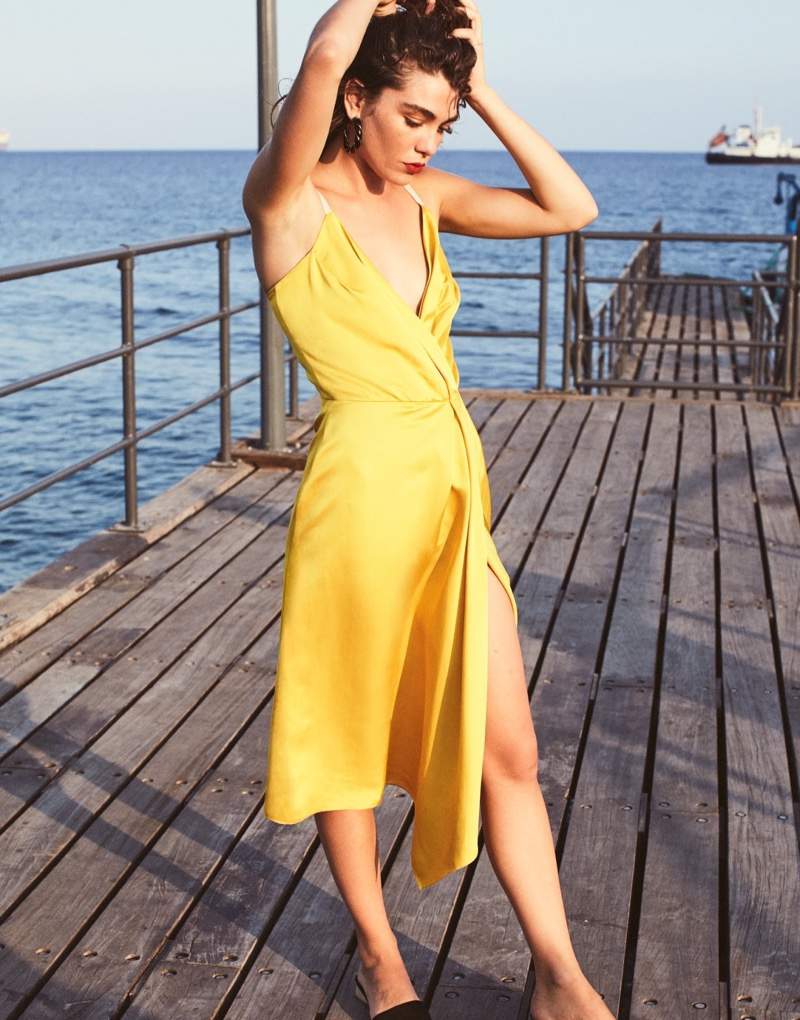 Embracing shades of yellow, the model wears Victoria Beckham dress and Aurelie Bidermann earrings