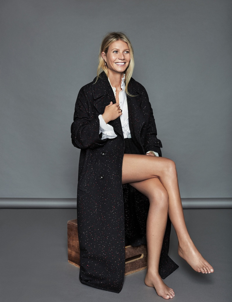 Taking a seat, Gwyneth Paltrow poses in Stella McCartney coat and blouse with Tous jewelry