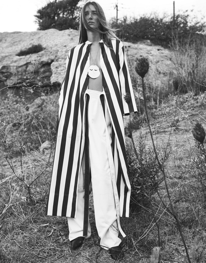 Photographed in black and white, the model wears Joseph robe, Tibi pants, Vince shoes and J.W. Anderson necklace