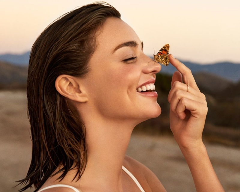 All smiles, Miranda Kerr poses with a butterfly on her nose for Marella campaign