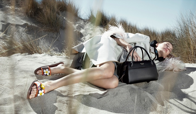 Lounging on the sand, Amanda Murphy appears in Prada's spring 2017 advertising campaign