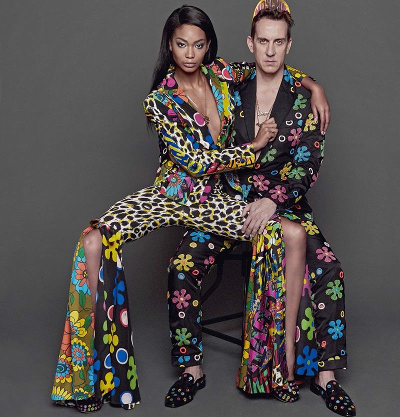 Model Chanel Iman and designer Jeremy Scott pose in pantsuits from Moschino's resort 2017 collection