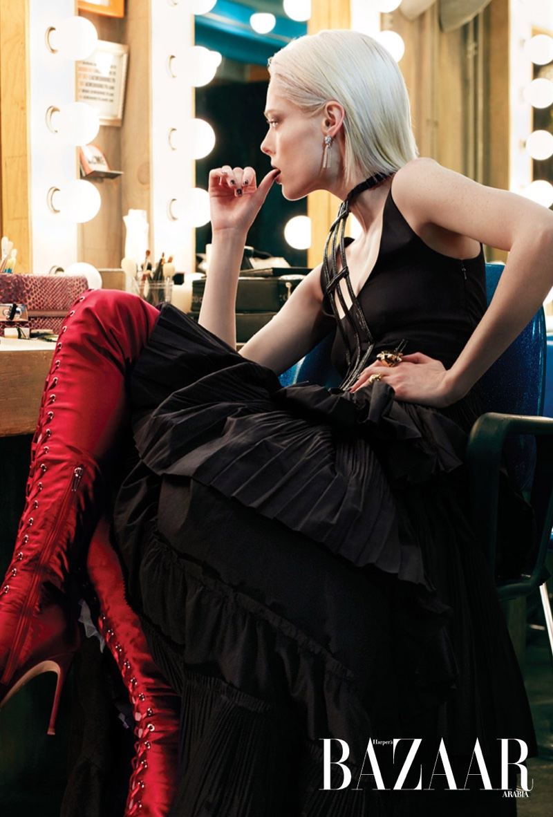 Posing backstage, Coco Rocha models black dress with red lace-up boots