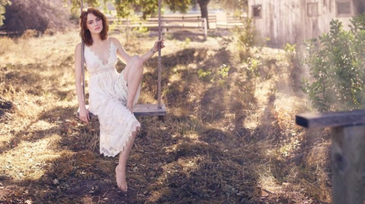 Posing on a swing, Emma Stone wears white crochet lace dress