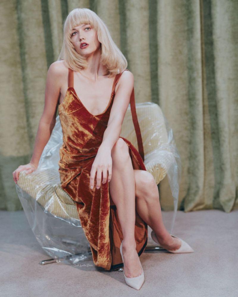 Flaunting her legs, Karlie Kloss poses in a burnt orange velvet dress