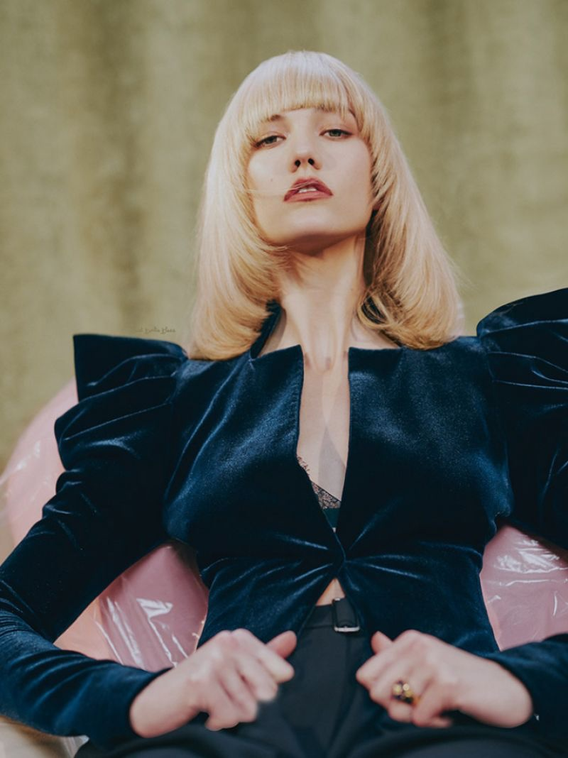 Showing off a platinum blonde hairstyle with fringe, Karlie Kloss wears a velvet jacket