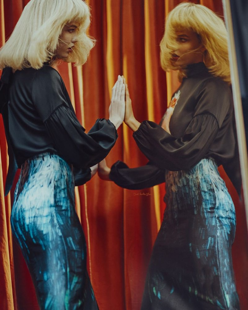 Looking in the mirror, Karlie Kloss models a black blouse and metallic skirt