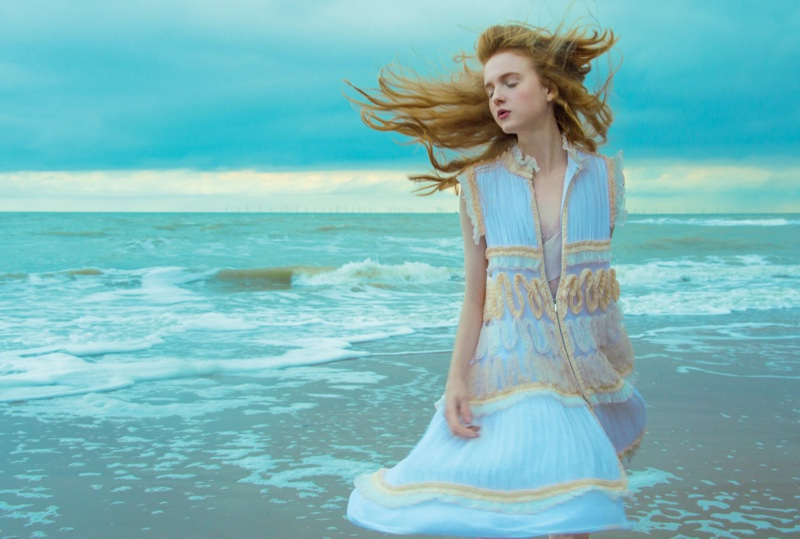 Catching the sea breeze, the model wears Chanel sleeveless coat and georgette slip dress