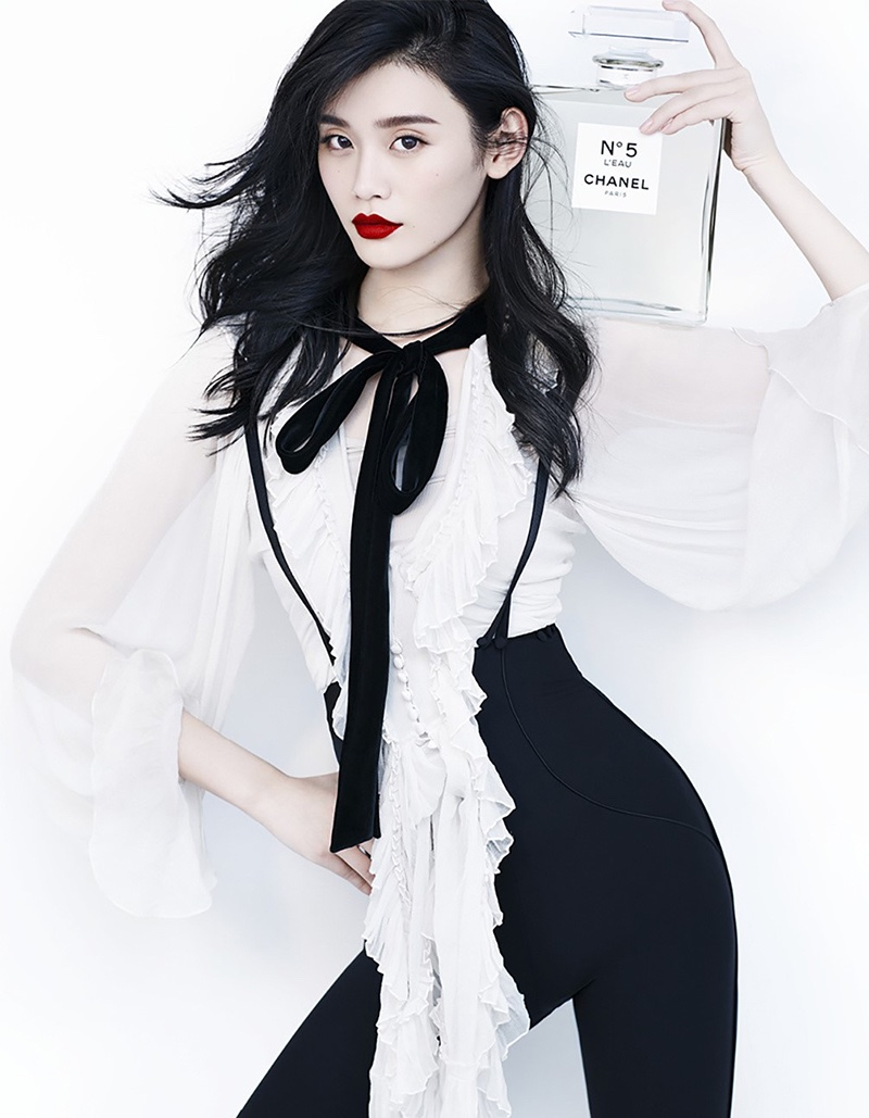 Ming Xi models Chanel top and pants with Chanel No. 5 perfume bottle