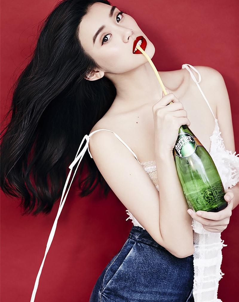 Taking a sip of sparkling water, Ming Xi models denim