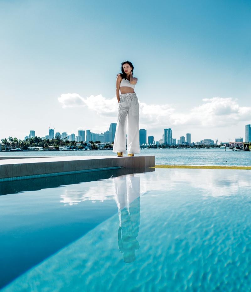Posing poolside, Adriana Lima wears Sportmax cropped tank, pants and rope belt