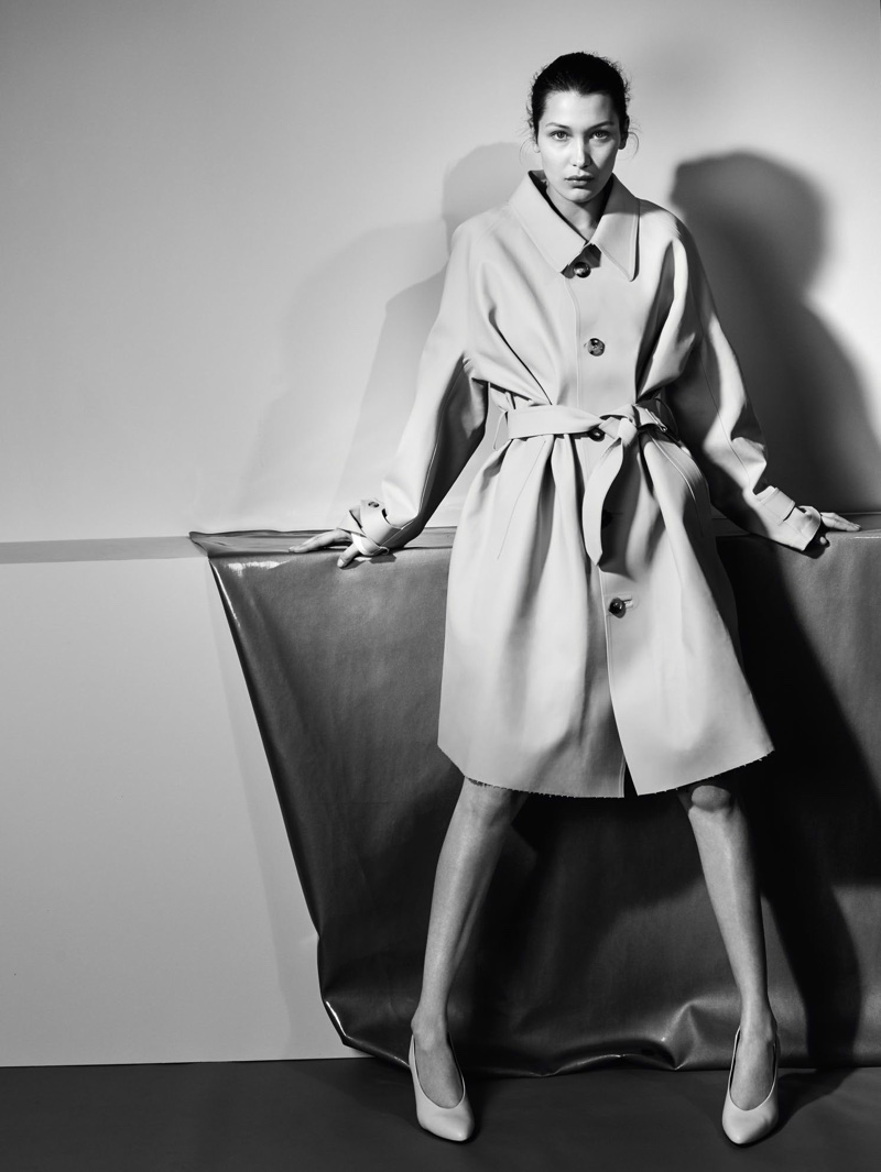 Captured in black and white, Bella Hadid poses in trench coat